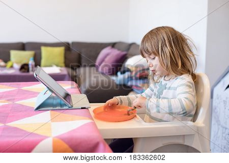 Little Child In High Chair Eating With Digital Tablet