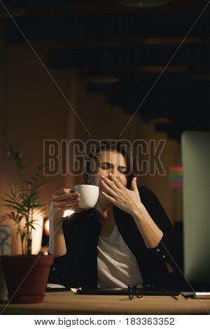 Image of yawning young woman designer sitting indoors at night using computer and drinking coffee.