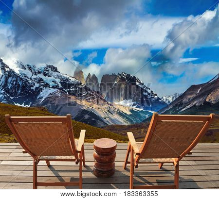 Two comfortable wooden sun loungers with views of the Torres Rocks. Torres del Paine National Park. Summer in the south of Chile. The concept of extreme tourism