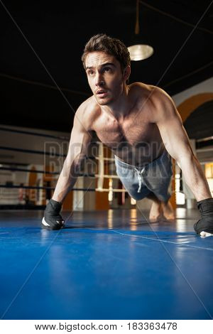 Strong man pushing up while training in the gym