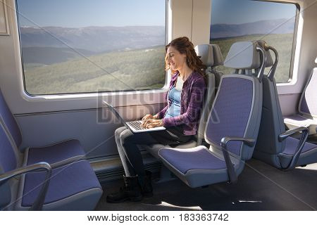 Side View Of Woman In Train Typing On Laptop Computer