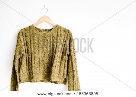 Front view of beauty trendy green female sweater on hanger near white background. Fashion concept.
