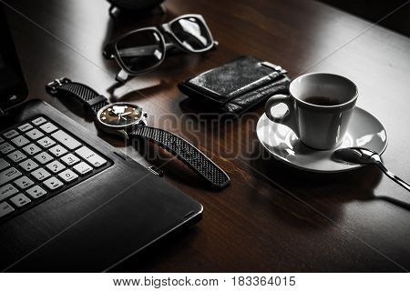 Office caffee brake. Computer laptop watch glasses wallet and coffe on the wooden table.