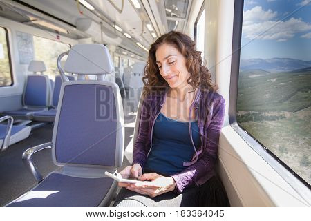 Smiling Woman Sitting In Train Typing On Smartphone
