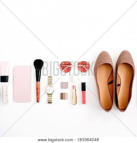 Beauty blog fashion concept. Female pink styled accessories: cell phone watches sunglasses cosmetics shoes on white background. Flat lay top view trendy feminine background.