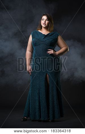 Plus size fashion model in green evening dress fat woman on black studio background overweight female body full length portrait