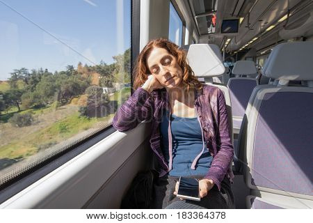 Woman In Train Sleeping With Mobile Phone In Hands
