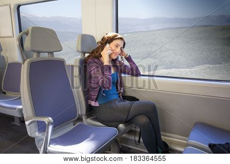 Woman Sitting In Train Talking On Mobile