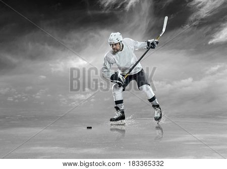 Ice hockey player in action on the ice under sky with clouds, outdoors