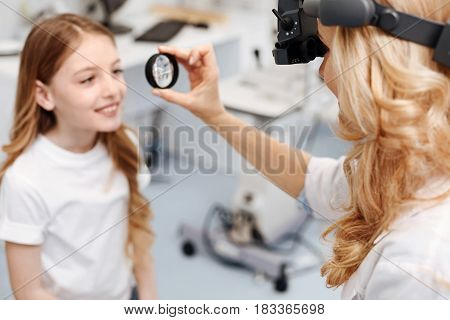 Perfect patient. Lively pretty beautiful child following doctors instructions while getting her eyesight checked using professional tools