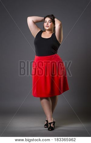 Plus size fashion model in red skirt fat woman on gray studio background overweight female body full length portrait