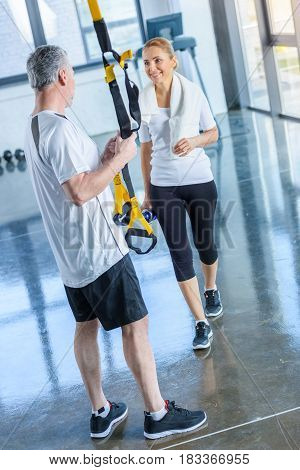 Sportswoman Holding Sport Bottle And Senior Sportsman With Resistance Band Talking In Sports Center