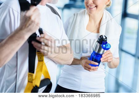 Sportswoman Holding Sport Bottle And Sportsman With Resistance Band Talking In Sports Center