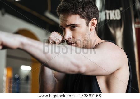 Portrait of boxer trying to kicking punching bag in gym while training
