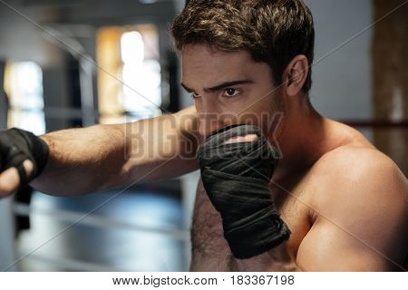 Photo of young strong sports man boxer make exercises in gym and looking aside