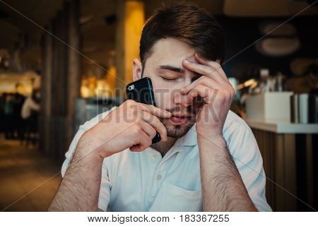 frustrated young businessman with a beard talking on the phone in the cozy restaurant