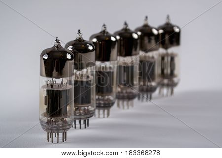 Row  of old glass vacuum radio tubes on white background. Selective focus