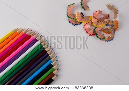 Multicolored pencils and pencil shaves on white background. Copy space
