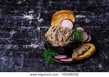 Liver pate with toast and radish on a dark background. Selective focus.