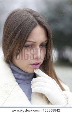 Portrait of upset and worried young woman standing in the park