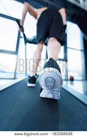 Close-up Partial View Of Mature Man In Sportswear Exercising On Treadmill In Gym