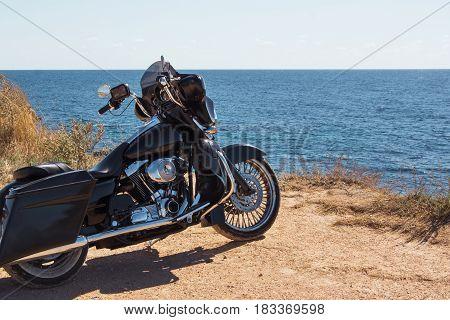 Black motorcycle on beautiful seacoast and blue sky onward. Prairie, steppe, summer.