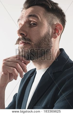 Young attractive macho stylish fashionable guy. Portrait on white background. Concept of narcissism