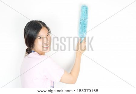 Asian house cleaner using dust cleaner on the wall