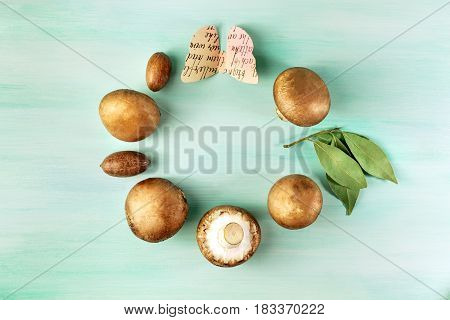 An overhead photo of portobello mushrooms with pecan nuts, bay leaves, and a paper butterfly, forming a circular frame for text on a teal wooden texture