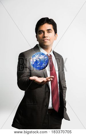 indian young businessman looking at a floating blue globe or earth model over right palm  while wearing complete corporate dress or attire like suit and tie, isolated over white background