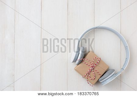 Top View Of Gift Box With Headphones On Wooden Table