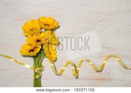 Wrapping yellow flowers gift over wooden background.