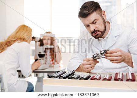 Helping little patient. Busy determined prominent optician arranging a special test spectacles for a patient while his colleague examining her eyesight using professional equipment