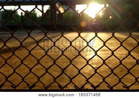 Chain Link Fence with Sun Flare Background.