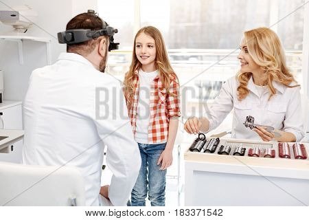 Tell me everything. Excellent handsome medical expert talking to little girl telling her what to do while she following doctors instructions