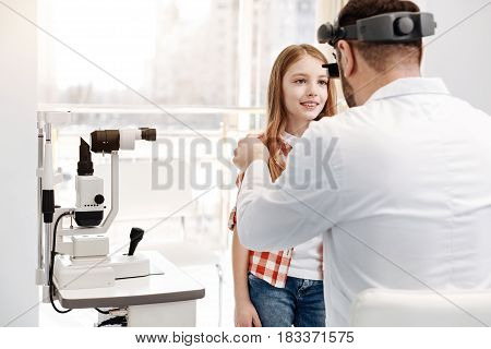 Hold your head up. Pretty clever young lady behaving nicely and following ophthalmologists instructions while he studying her eyes
