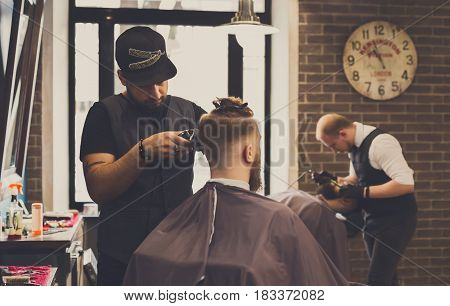 Man getting haircut by hairstylist at barbershop. Stylish barber and client in mirrow poster