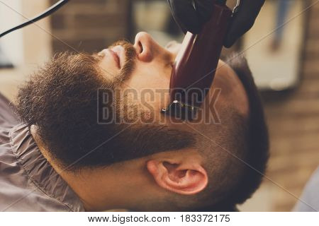 Barber styling beard with trimmer at barbershop, closeup. Barbershop for men