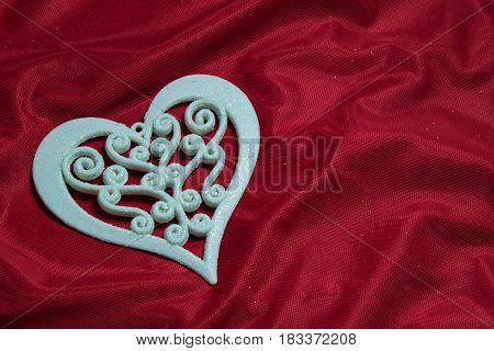 one beautiful white carved openwork heart on a red background