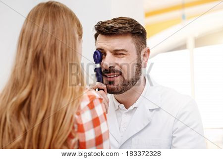 Try not to move your eyes. Prominent capable handsome guy employing professional ophthalmoscope for indicating problems and diagnosing his patient
