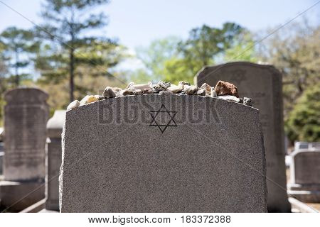 Headstone in a Jewish cemetery with Star of David and memory stones. Selective focus on the foreground. Copy space.