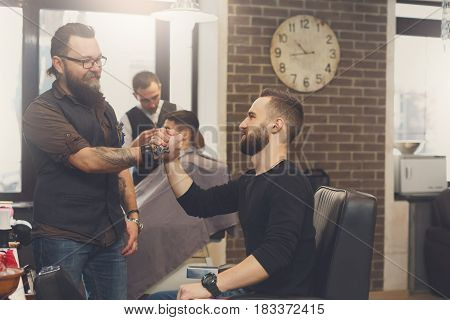 Thankful bearded client and professional stylish barber shaking hands after haircut. Hairstylist and satisfied customer handshaking at barbershop