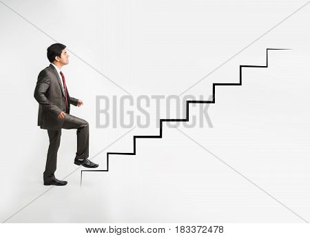 indian young businessman climbing artificial ladder or staircase achieving goal while wearing complete corporate attire like suit and tie, isolated over white background