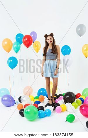 Girl in summer outfut, wearing skirt and top, posing with balloons with helium gel