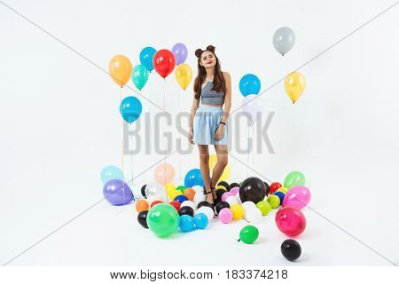 Pretty young girl looking straight posing with coloured balloons with helium on white background