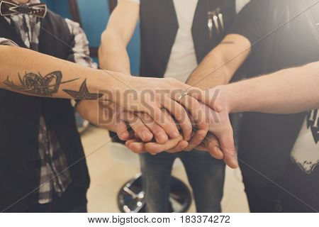 Men friendship. United hands of young team with tattoo. Unity and teamwork concept