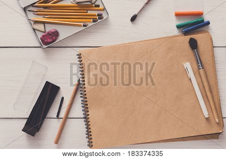 Artist working space background. Watercolor paints and blank craft paper on white wooden desk, top view, flat lay, copy space