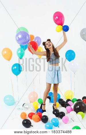 Young beautiful woman on high heels looks happy playing with coloured balloons on white background