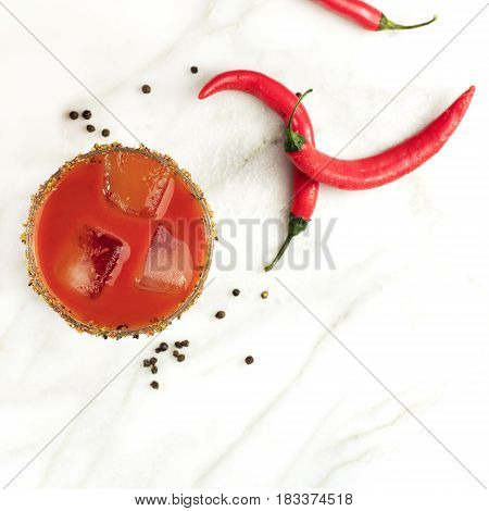 A square photo of a Bloody Mary cocktail, shot from above on a white marble texture, with red hot chili peppers and copy space. Selective focus