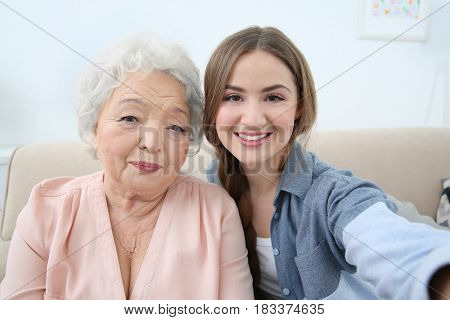 Beautiful girl with grandmother taking selfie on couch at home